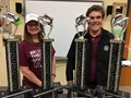 Mrs. Fancher and Mr. Komperda display the trophies won by the RRMS choir and band.