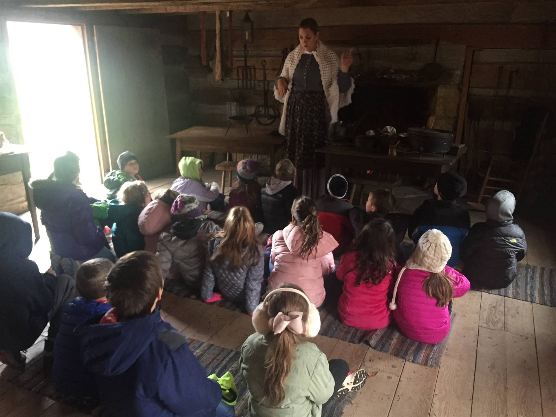 Children listening to log cabin presentation at Hale Farm