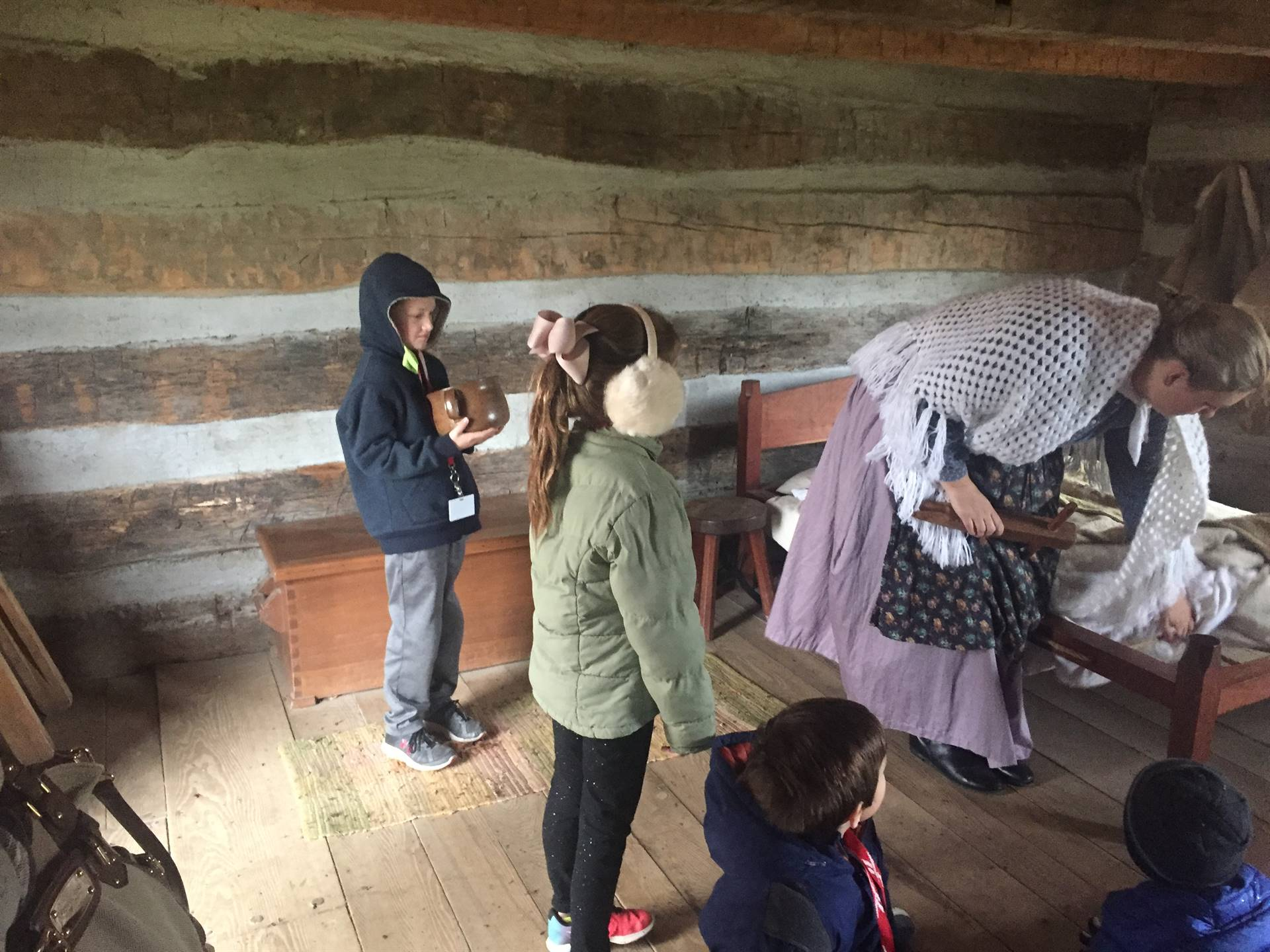 Students and guide in log cabin