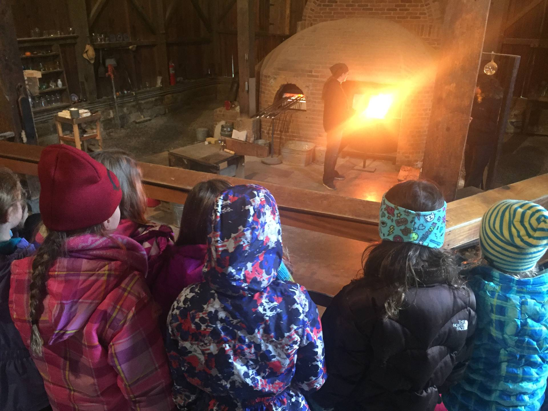 Students watching a glass blower make a Christmas ornament at Hale Farm