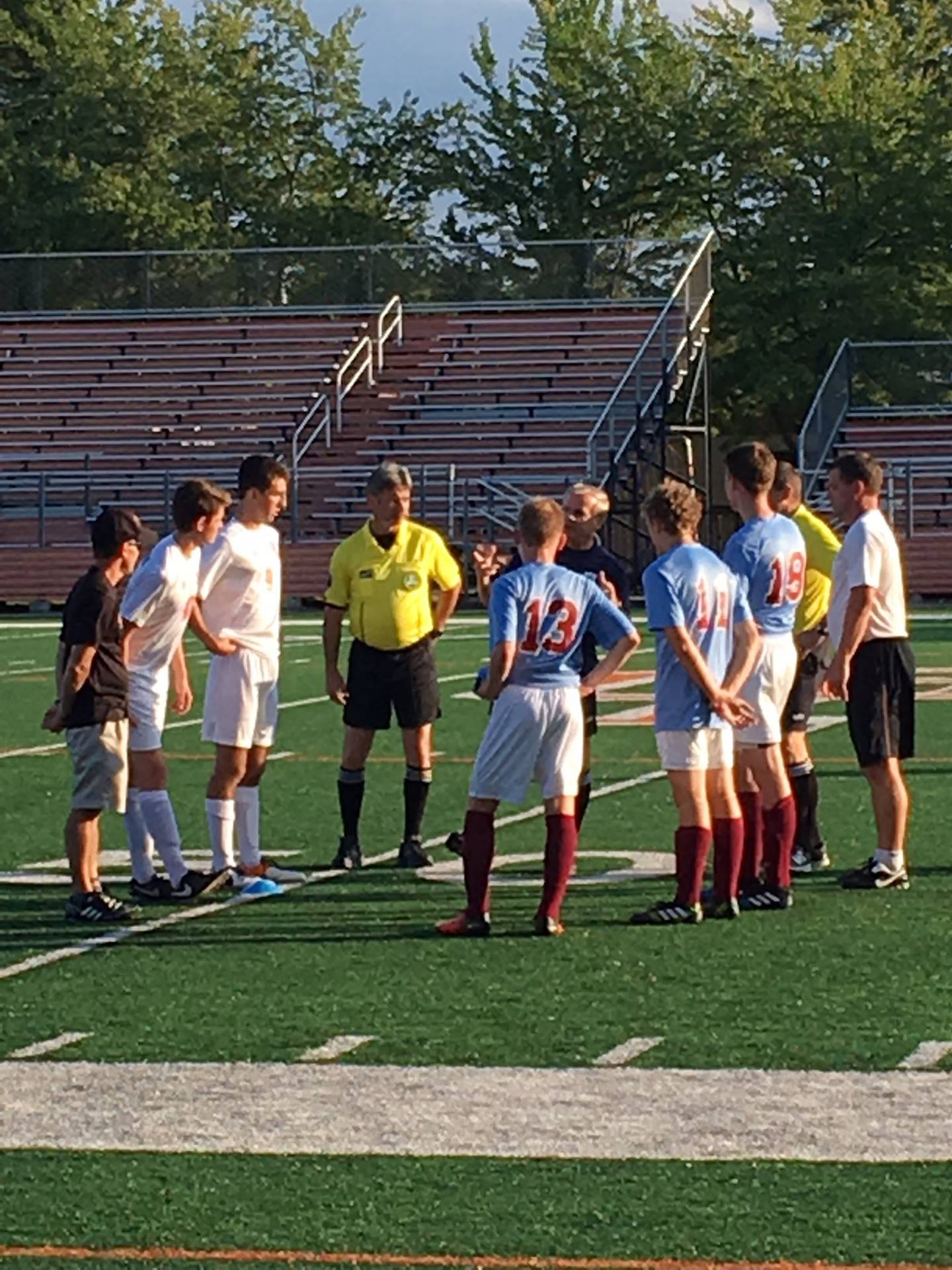 The Chagrin Falls and River Varsity captains and coaches attend the pregame talk and coin toss.