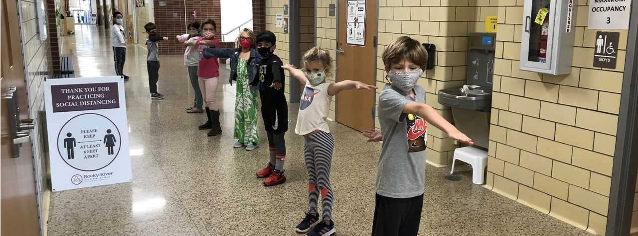 Second graders show us how to social distance in the hallways