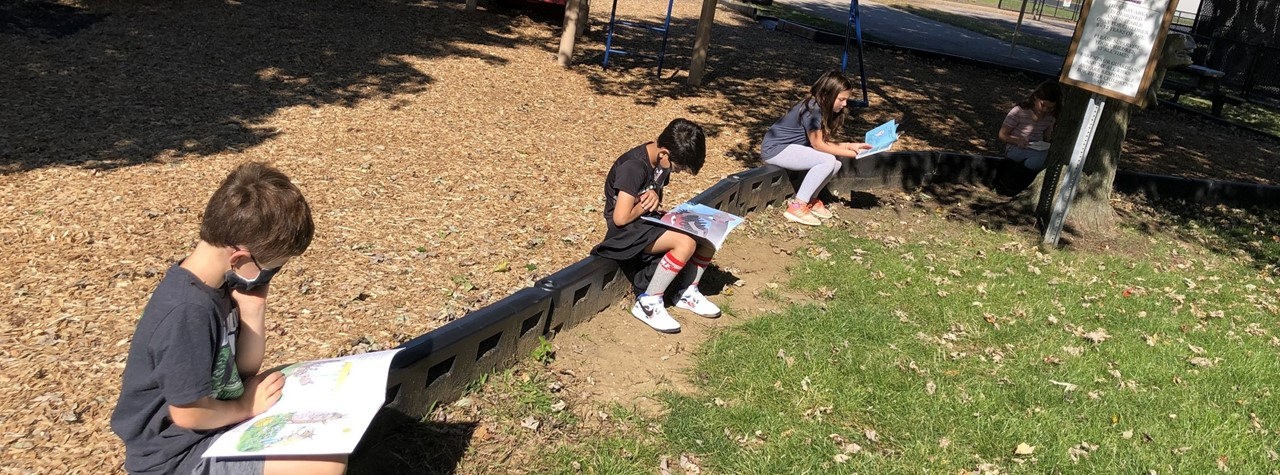 Mrs. Hughes' class takes a break outside to read and relax